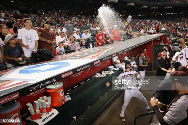 David Peralta of the Arizona Diamondbacks throws water onto fans before the start of the MLB game against the St Louis Cardinals at Chase Field on...