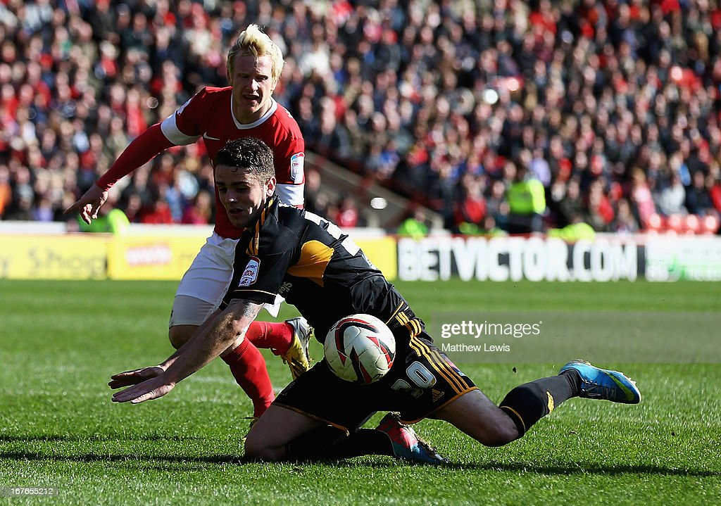 David Perkins of Barnsley and Robbie Brady of Hull City challenge for the ball during the npower Championship match between Barnsley and Hull City at Oakwell Stadium on April 27, 2013 in Barnsley, England.