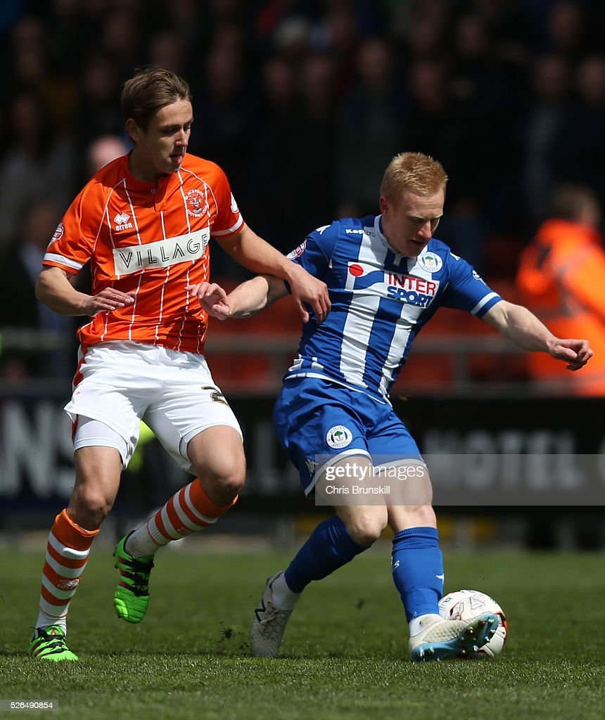 David Perkins of Wigan Athletic holds off Liam Smith of Blackpool during the Sky Bet League One match between Blackpool and Wigan Athletic at Bloomfield Road on April 30, 2016 in Blackpool, England.