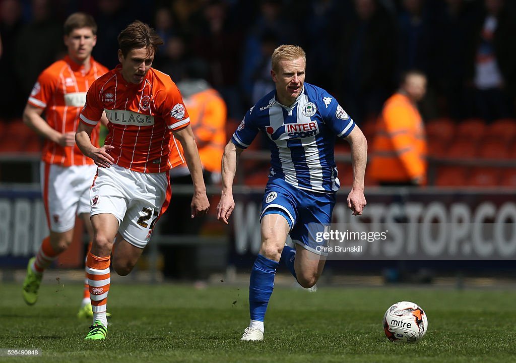 David Perkins of Wigan Athletic is chased by Liam Smith of Blackpool during the Sky Bet League One match between Blackpool and Wigan Athletic at Bloomfield Road on April 30, 2016 in Blackpool, England.