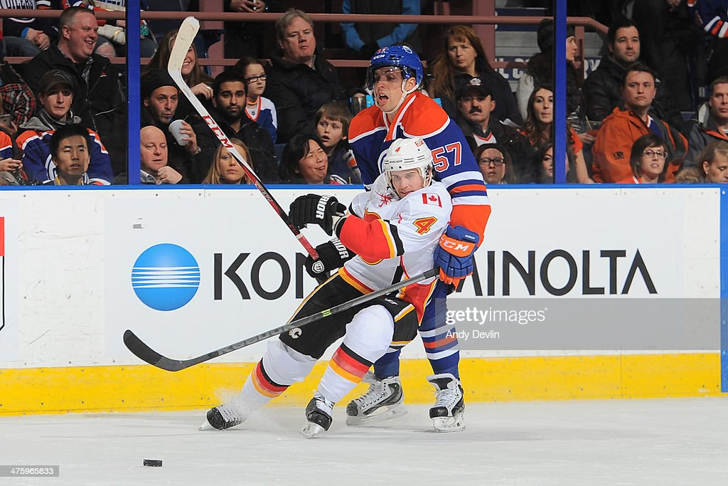 <a gi-track='captionPersonalityLinkClicked' href=/galleries/search?phrase=David+Perron&family=editorial&specificpeople=4282591 ng-click='$event.stopPropagation()'>David Perron</a> #57 of the Edmonton Oilers battles for the puck against <a gi-track='captionPersonalityLinkClicked' href=/galleries/search?phrase=Kris+Russell&family=editorial&specificpeople=879805 ng-click='$event.stopPropagation()'>Kris Russell</a> #4 of the Calgary Flames on March 1, 2014 at Rexall Place in Edmonton, Alberta, Canada.