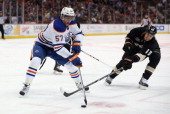 David Perron of the Edmonton Oilers is pursued by Ryan Getzlaf of the Anaheim Ducks for the puck in the first period at Honda Center on January 3...