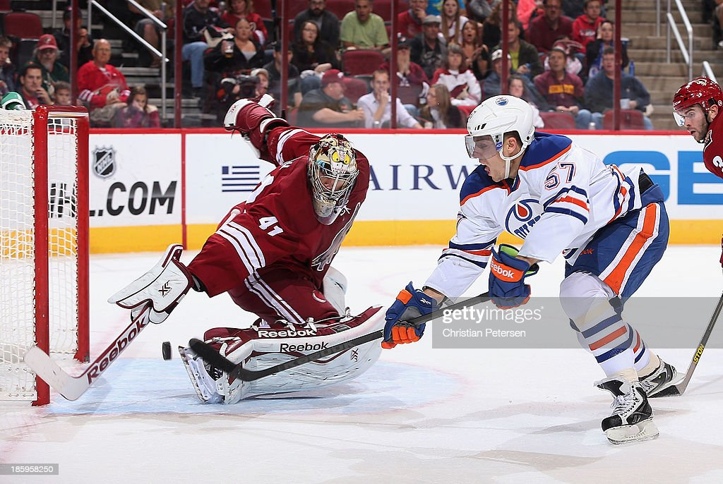 David Perron of the Edmonton Oilers shoots the puck on goaltender Mike Smith of the Phoenix Coyotes during the second period of the NHL game at...