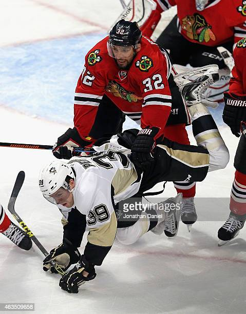 David Perron of the Pittsburgh Penguins is dumped by Michal Rozsival of the Chicago Blackhawks in front of the goal at the United Center on February...
