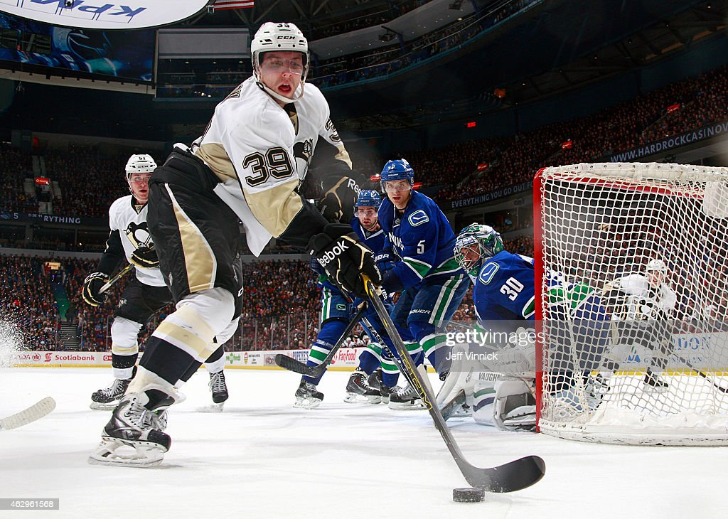 David Perron of the Pittsburgh Penguins plays the puck behind Ryan Miller of the Vancouver Canucks during their NHL game at Rogers Arena February 7...