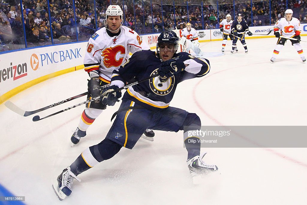 <a gi-track='captionPersonalityLinkClicked' href=/galleries/search?phrase=David+Perron&family=editorial&specificpeople=4282591 ng-click='$event.stopPropagation()'>David Perron</a> #57 of the St. Louis Blues and <a gi-track='captionPersonalityLinkClicked' href=/galleries/search?phrase=Dennis+Wideman&family=editorial&specificpeople=575234 ng-click='$event.stopPropagation()'>Dennis Wideman</a> #26 of the Calgary Flames chase down a loose puck during the third period at the Scottrade Center on April 25, 2013 in St. Louis, Missouri. The Blues beat the Flames 4-1.