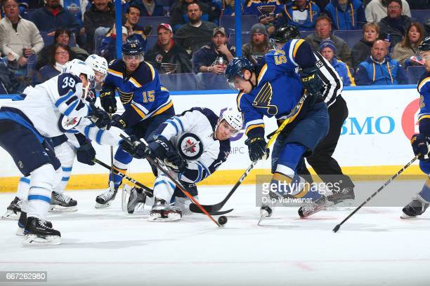 David Perron of the St Louis Blues in action against Adam Lowry of the Winnipeg Jets t the Scottrade Center on December 3 2016 in St Louis Missouri