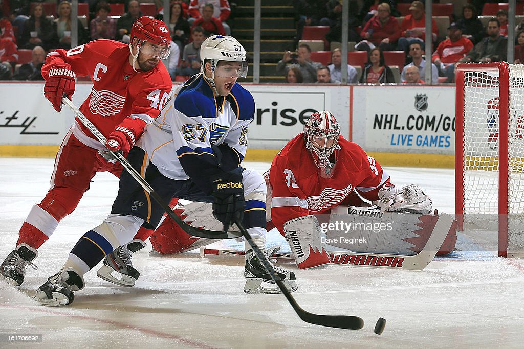 David Perron #57 of the St Louis Blues tries to control the puck in front of Henrik Zetterberg #40 and Jimmy Howard #35 of the Detroit Red Wings during a NHL game at Joe Louis Arena on February 13, 2013 in Detroit, Michigan. The Blues won in overtime 4-3