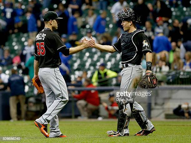 David Phelps and JT Realmuto of the Miami Marlins celebrate after beating the Milwaukee Brewers 75 at Miller Park on April 30 2016 in Milwaukee...