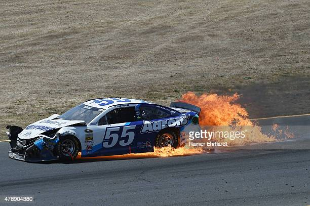 David Ragan driver of the Aaron's Dream Machine Toyota catches on fire during the NASCAR Sprint Cup Series Toyota/Save Mart 350 at Sonoma Raceway on...