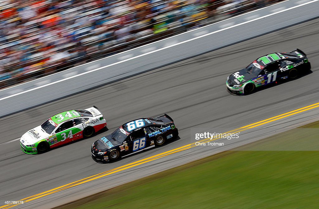 David Ragan, driver of the #34 Farm Rich Ford, leads Michael Waltrip, driver of the #66 RoyalTeakCollection.com Toyota, and Denny Hamlin, driver of the #11 FedEx Ground Toyota, during the NASCAR Sprint Cup Series Coke Zero 400 at Daytona International Speedway on July 6, 2014 in Daytona Beach, Florida.