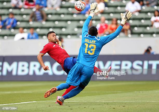 David Ramirez of Costa Rica gets the ball over goalkeeper Dwayne Miller of Jamaica to score a goal in the first half of their CONCACAF Gold Cup Group...