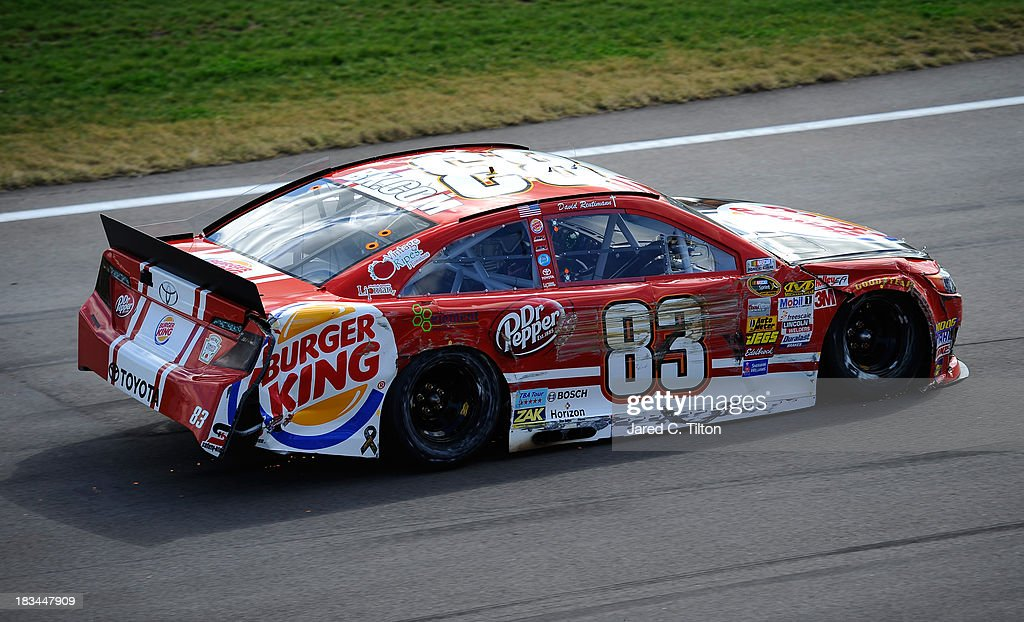 David Reutimann, driver of the #83 Burger King / Dr Pepper Toyota, drives his damaged car after an incident during the NASCAR Sprint Cup Series 13th Annual Hollywood Casino 400 at Kansas Speedway on October 6, 2013 in Kansas City, Kansas.