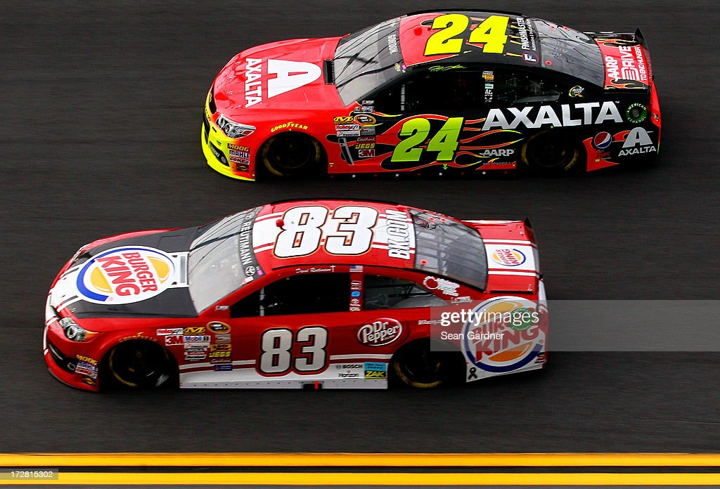 David Reutimann, driver of the #83 Burger King / Dr. Pepper Toyota, drives with Jeff Gordon, driver of the #24 Axalta Coating Systems Chevrolet, during practice for the NASCAR Sprint Cup Series Coke Zero 400 at Daytona International Speedway on July 4, 2013 in Daytona Beach, Florida.