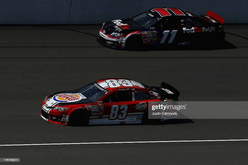 David Reutimann, driver of the #83 Burger King / Dr. Pepper Toyota, races Denny Hamlin, driver of the #11 FedEx Freight Toyota, during the NASCAR Sprint Cup Series 44th Annual Pure Michigan 400 at Michigan International Speedway on August 18, 2013 in Brooklyn, Michigan.