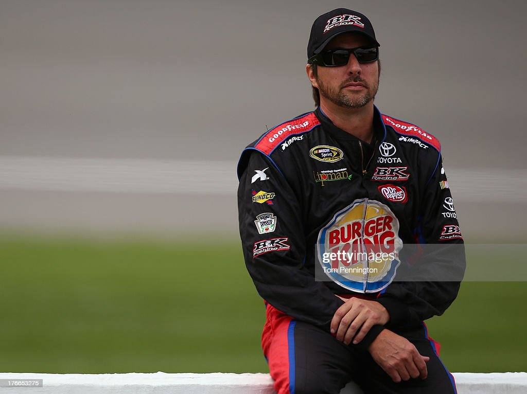 David Reutimann, driver of the #83 Burger King / Dr. Pepper Toyota, sits on the pit wall during qualifying for the NASCAR Sprint Cup Series 44th Annual Pure Michigan 400 at Michigan International Speedway on August 16, 2013 in Brooklyn, Michigan.