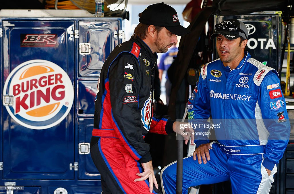 David Reutimann, driver of the #83 Burger King / Dr. Pepper Toyota, talks with David Stremme, driver of the #30 Lean1 Toyota, in the garage area during practice for the NASCAR Sprint Cup Series 44th Annual Pure Michigan 400 at Michigan International Speedway on August 17, 2013 in Brooklyn, Michigan.