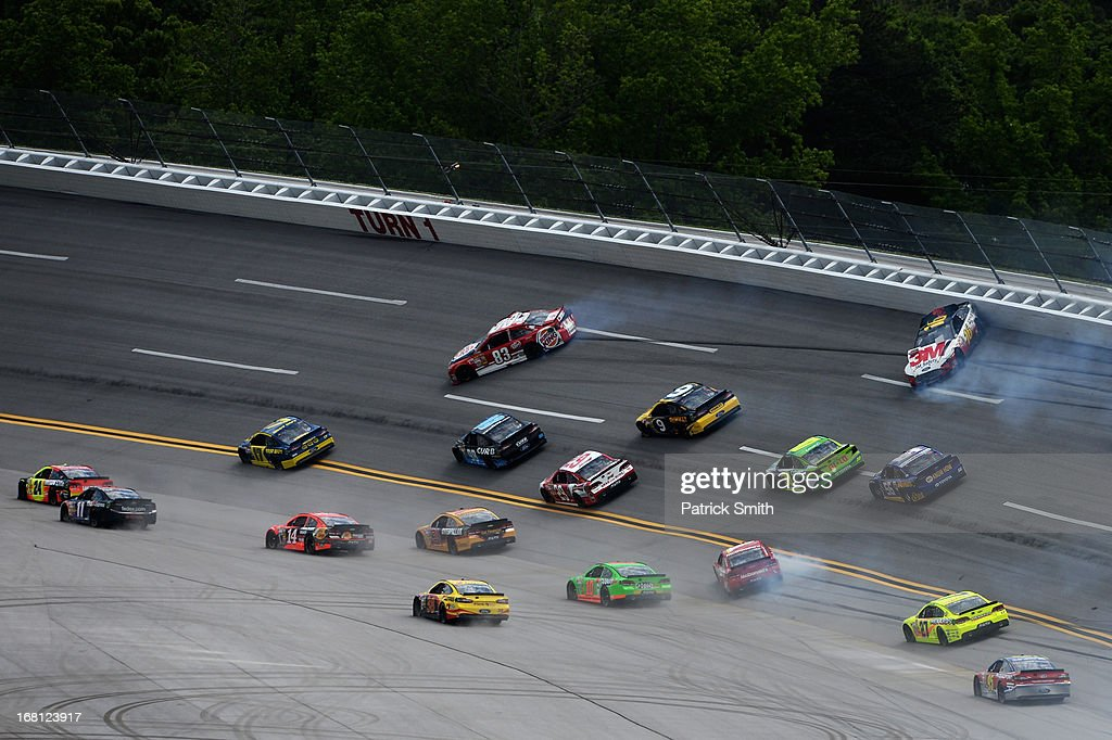 David Reutimann, driver of the #83 Burger King/Dr. Pepper Toyota, and Greg Biffle, driver of the #16 3M Safety Ford, slide out of control as other drivers avoid them in turn one during the NASCAR Sprint Cup Series Aaron's 499 at Talladega Superspeedway on May 5, 2013 in Talladega, Alabama.
