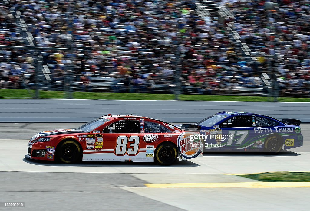 David Reutimann, driver of the #83 Burger King/Dr Pepper Toyota, races Ricky Stenhouse Jr., driver of the #17 Fifth Third Ford, during the NASCAR Sprint Cup Series STP Gas Booster 500 on April 7, 2013 at Martinsville Speedway in Ridgeway, Virginia.