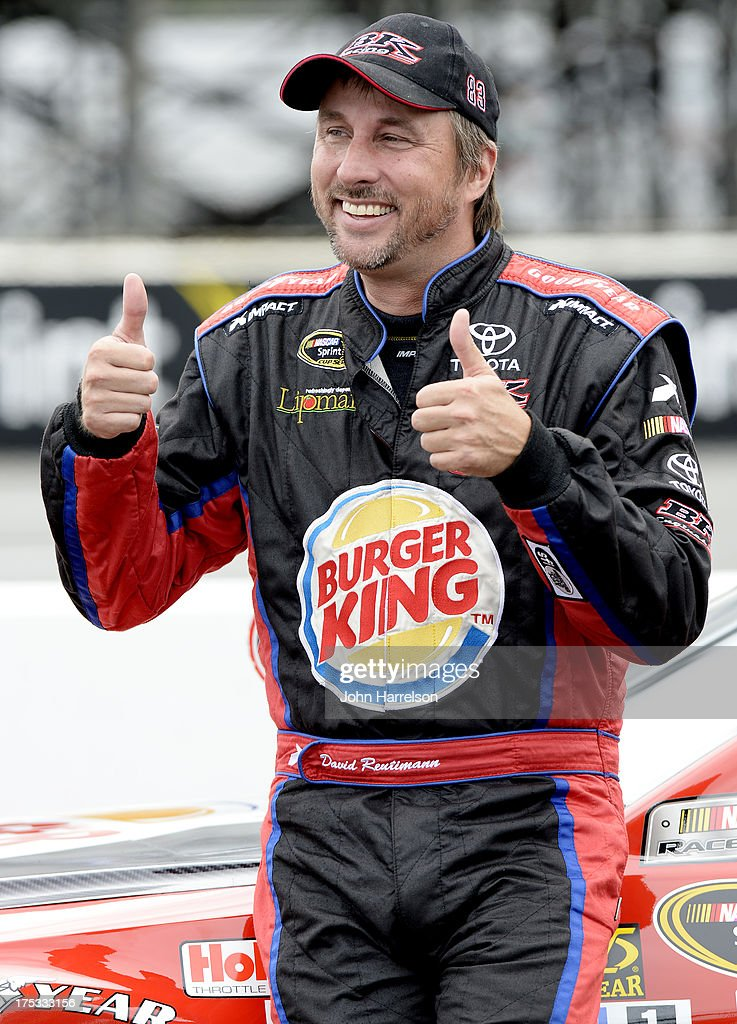 David Reutimann, driver of the #83 Burger King/Dr. Pepper Toyota, stands by his car during qualifying for the NASCAR Sprint Cup Series GoBowling.com 400 at Pocono Raceway on August 2, 2013 in Long Pond, Pennsylvania.