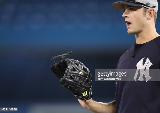 David Robertson of the New York Yankees shows off a dragonfly during batting practice before the start of MLB game action against the Toronto Blue...