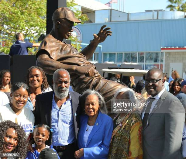 David Robinson a son of Jackie Robinson poses in front of the new statue of his father with its sculptor Branly Cadet at Dodger Stadium in Los...