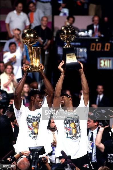 David Robinson holds up the NBA Championship trophy as Tim Duncan of the San Antonio Spurs holds up the MVP after winning Game Five of the 1999 NBA...