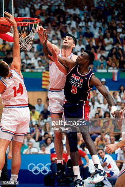 David Robinson of the United States goes up for a rebound against Stojan Vrankovic and Dino Radja of Croatia during the 1992 Olympic game against...