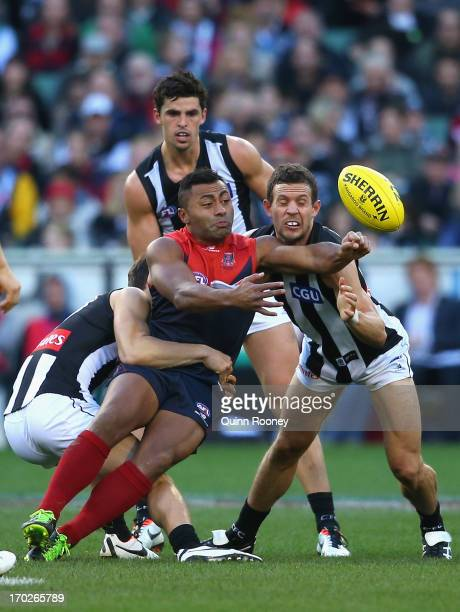 David Rodan of the Demons handballs whilst being tackled by Ben Kennedy and Luke Ball of the Magpies during the round 11 AFL match between the...