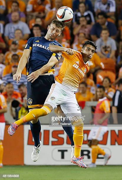 David Romney#67 of the Los Angeles Galaxy battles for the ball with Leonel Miranda of the Houston Dynamo at BBVA Compass Stadium on July 25 2015 in...