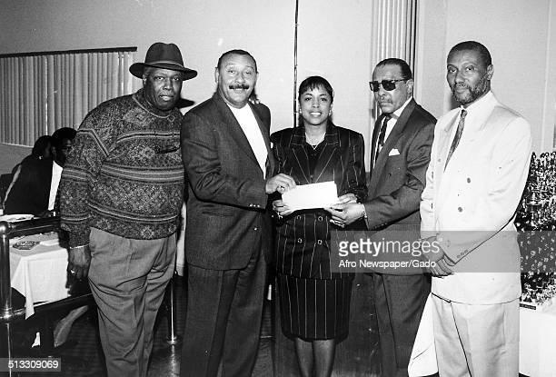 David Rose Bob Mcquaige Reggie Thomas Clayton Tucker and Wesley Johnson presenting a check at the Sportsmans Basketball League May 23 1996