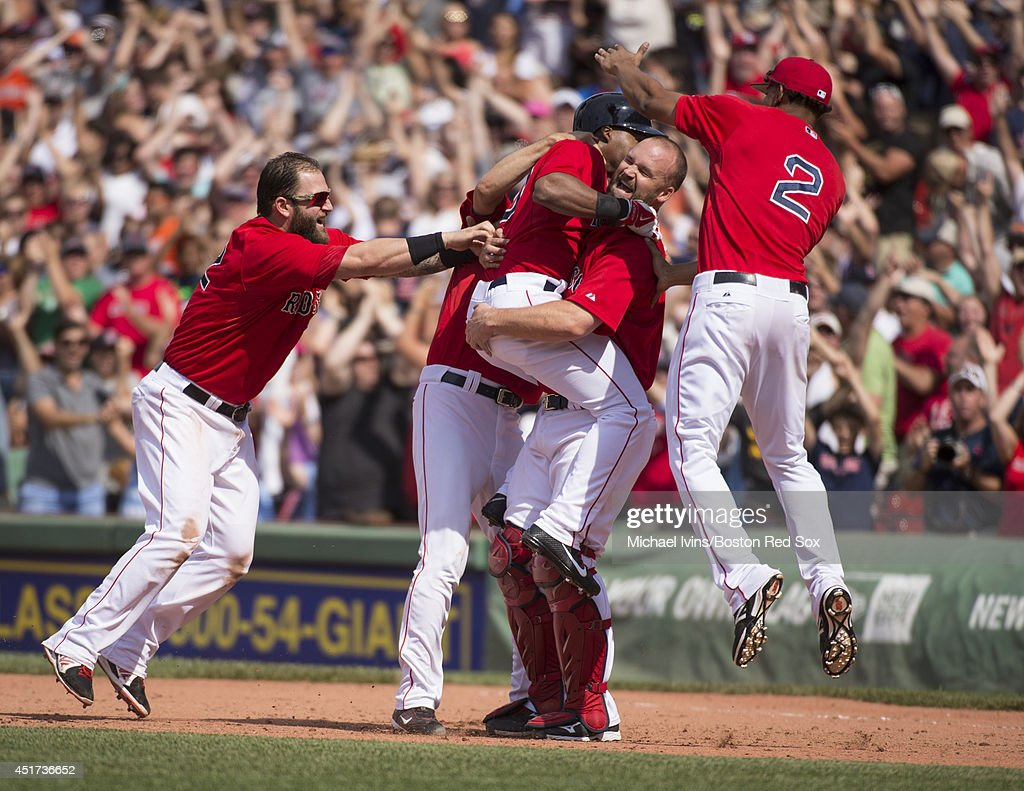 David Ross Mike Napoli and Xander Bogaerts of the Boston Red Sox swarm Jonathan Herrera after he hit a walkoff single against the Baltimore Orioles...