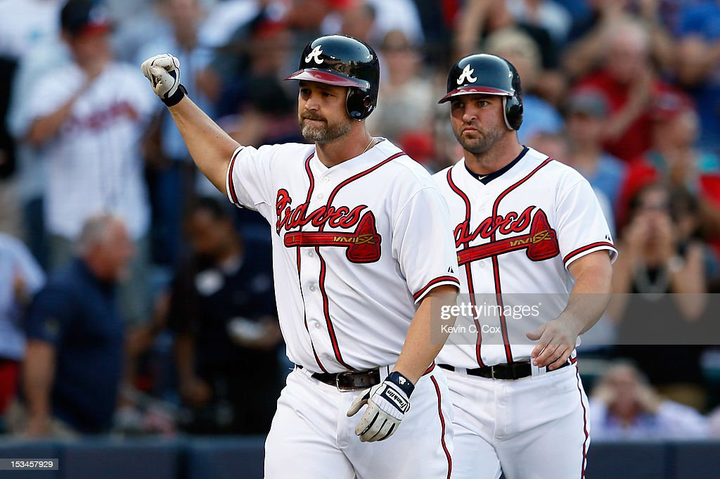 <a gi-track='captionPersonalityLinkClicked' href=/galleries/search?phrase=David+Ross&family=editorial&specificpeople=210843 ng-click='$event.stopPropagation()'>David Ross</a> #8 of the Atlanta Braves reacts as he heads back to the dugout in front of teammate <a gi-track='captionPersonalityLinkClicked' href=/galleries/search?phrase=Dan+Uggla&family=editorial&specificpeople=542208 ng-click='$event.stopPropagation()'>Dan Uggla</a> #26 after Ross hits a two-run home run in the second inning against the St. Louis Cardinals during the National League Wild Card playoff game at Turner Field on October 5, 2012 in Atlanta, Georgia.