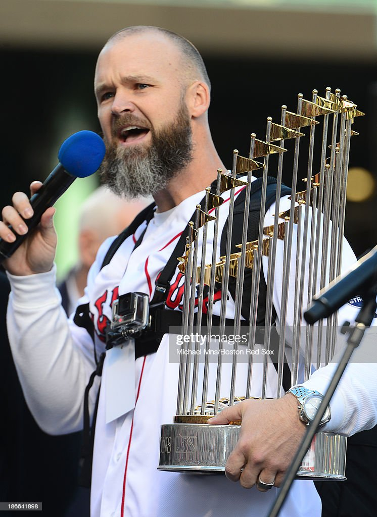 David Ross #3 of the Boston Red Sox addresses a crowd while holding the 2013 World Series trophy before the start of a victory parade on November 2, 2013 at Fenway Park in Boston, Massachusetts.