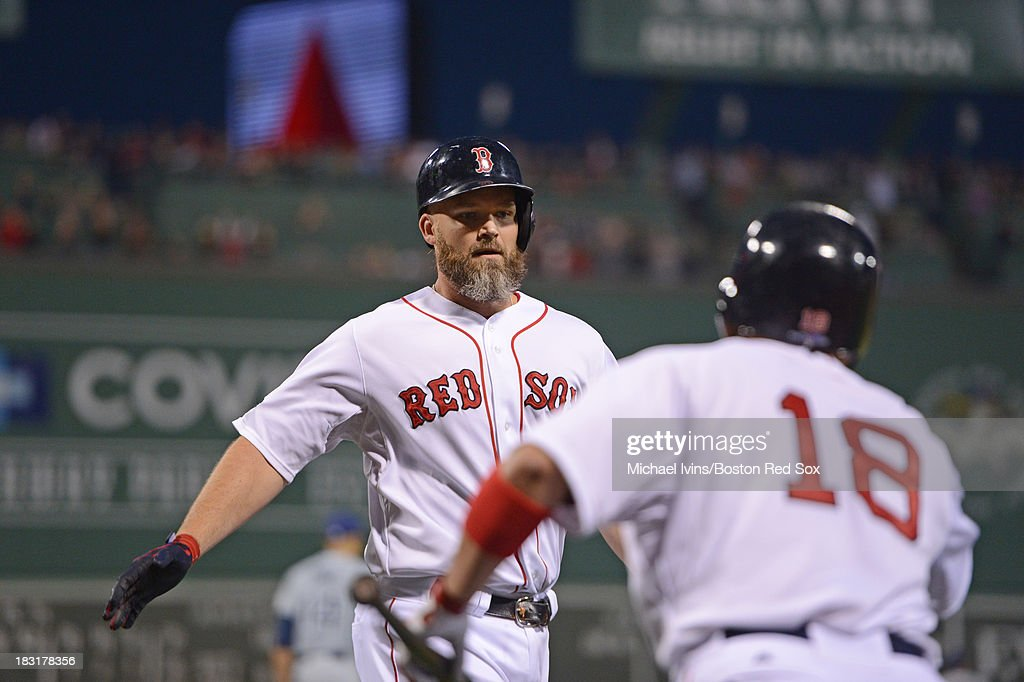David Ross #3 of the Boston Red Sox is congratulated by Shane Victorino #18 after scoring against the Tampa Bay Rays during the third inning of game two of the American League Division Series on October 5, 2013 at Fenway Park in Boston, Massachusetts.