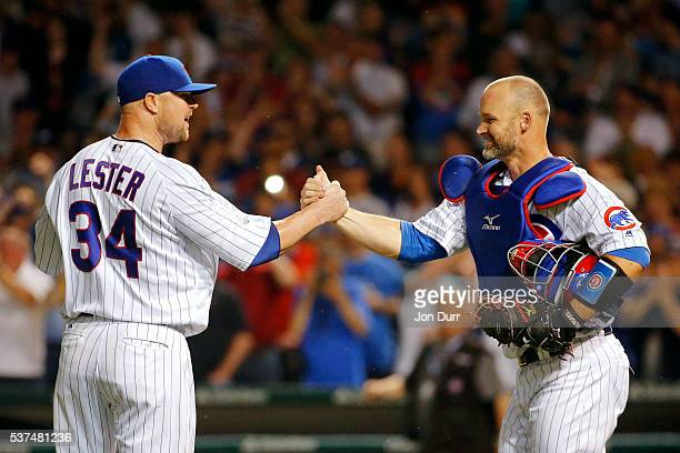 David Ross of the Chicago Cubs congratulates Jon Lester for pitching a complete game for the win against the Los Angeles Dodgers at Wrigley Field on...
