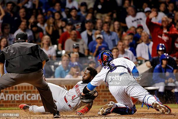 David Ross of the Chicago Cubs tags out Brandon Phillips of the Cincinnati Reds at home plate during the sixth inning at Wrigley Field on June 14...
