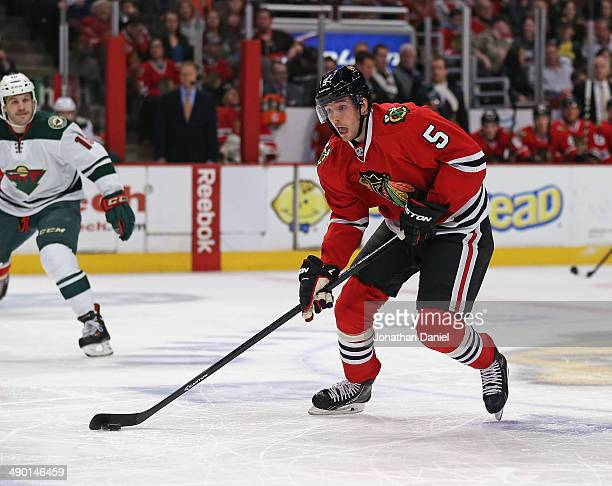 David Rundblad of the Chicago Blackhawks advances the puck past Jake Dowell of the Minnesota Wild at the United Center on April 3 2014 in Chicago...