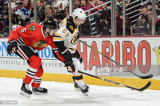 David Rundblad of the Chicago Blackhawks and Brian Ferlin of the Boston Bruins chase the puck during the NHL game at the United Center on February 22...