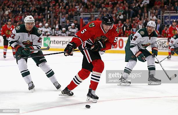 David Rundblad of the Chicago Blackhawks shoots between Nino Niederreiter and Kyle Brodziak of the Minnesota Wild at the United Center on April 7...