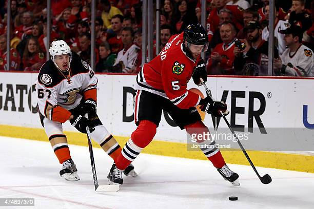 David Rundblad of the Chicago Blackhawks skates with the puck as Rickard Rakell of the Anaheim Ducks defends in Game Six of the Western Conference...
