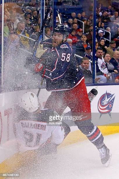 David Savard of the Columbus Blue Jackets checks Kyle Palmieri of the Anaheim Ducks into the boards while chasing after the puck during the third...