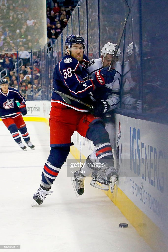 David Savard #58 of the Columbus Blue Jackets checks Trevor Lewis #22 of the Los Angeles Kings while chasing after the puck during the third period on December 20, 2016 at Nationwide Arena in Columbus, Ohio. Columbus defeated Los Angeles 3-2 in a shootout.