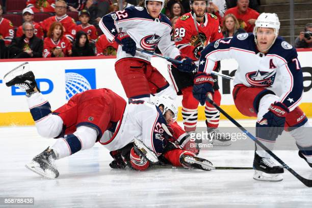 David Savard of the Columbus Blue Jackets crashes to the ice as Sonny Milano of the Columbus Blue Jackets and Ryan Hartman watch in the background in...