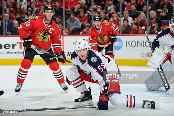 David Savard of the Columbus Blue Jackets gets in position to block the puck as Jonathan Toews of the Chicago Blackhawks watches from behind in the...