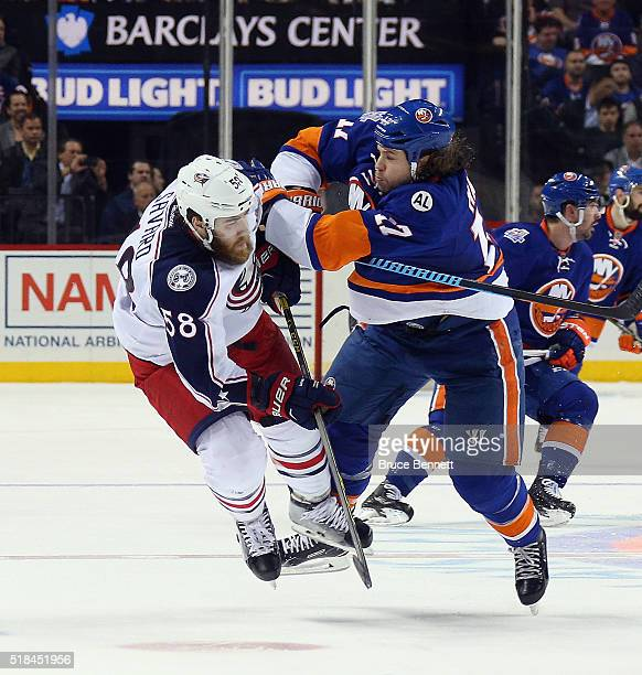 David Savard of the Columbus Blue Jackets is hit by Matt Martin of the New York Islanders during the second period at the Barclays Center on March 31...