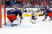 David Savard of the Columbus Blue Jackets knocks down Daniel Carcillo of the Chicago Blackhawks as he attempts to get a shot off on Sergei Bobrovsky...