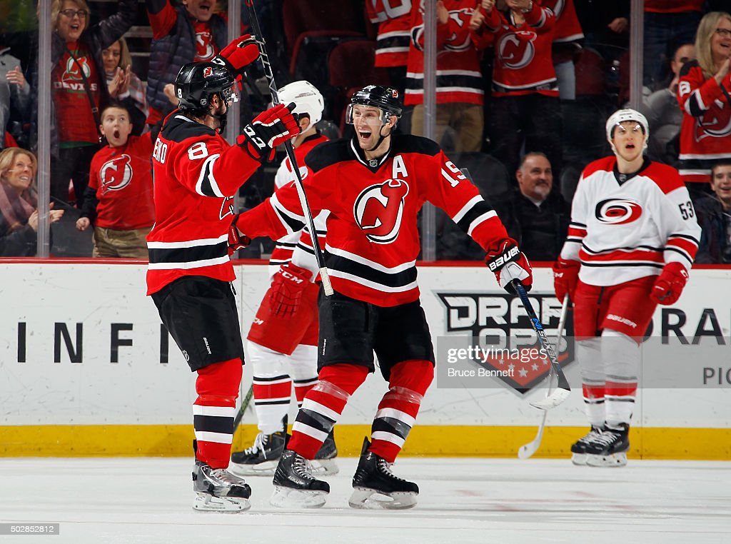 David Schlemko of the New Jersey Devils celebrates his game winning goal at 1655 of the third period against the Carolina Hurricanes and is joined by...