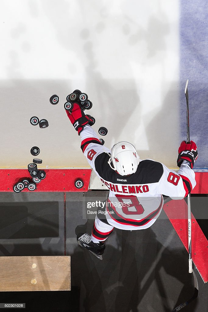 David Schlemko of the New Jersey Devils scatters pucks onto the ice during warmups before an NHL game against the Detroit Red Wings at Joe Louis...