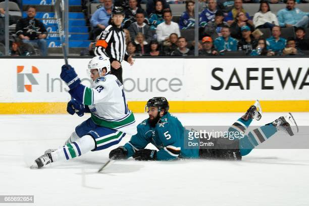 David Schlemko of the San Jose Sharks and Griffen Molino of the Vancouver Canucks take a tumble during a NHL game at SAP Center at San Jose on April...